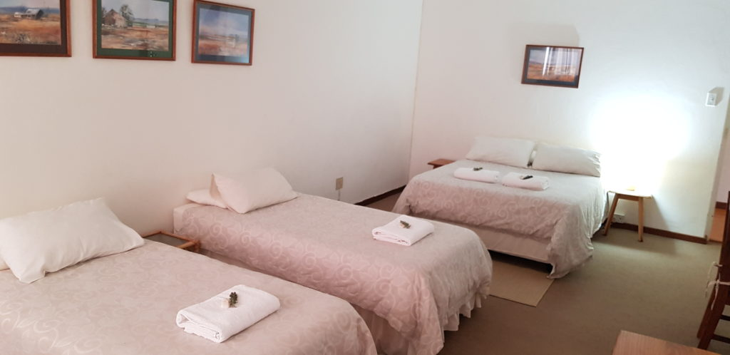 ROOM 3 HAS A DOUBLE BED AND TWO SINGLE BEDS, AND IS LINKED TO A PRIVATE EN-SUITE BATHROOM WITH BATH AND SHOWER.